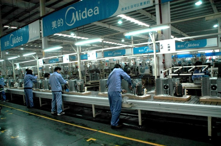 --FILE-- Chinese workers labor on the production line at a Midea air conditioner plant in Wuhan, central Chinas Hubei province, February 4, 2009.  GD Midea Holding Co. said it plans to raise 3 billion yuan (US$439.08 million) via a rights issue to finance the expansion of its business. The home appliance maker intends to issue 189 million shares, equivalent to 10 percent of its current equity interest, at 15.75 yuan each.