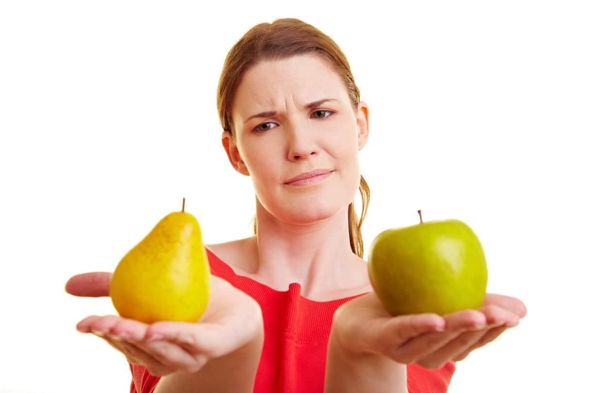 Junge Frau hält Apfel und Birne auf den Händen