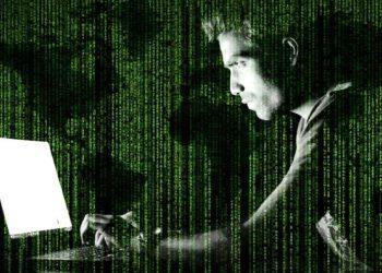 Hacker frente a computador, con código y mapa mundial. Imagen por Jack Moreh / stockvault.net