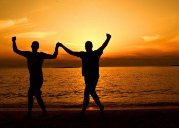 Dos hombres bailando a las orillas del mar bajo la puesta del sol. Fuente: Dana Tenis / Pexels.com.