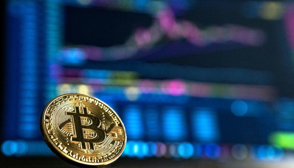 Un bitcoin delante de un tablero de análisis de mercado. Fuente: André François McKenzie/ Unsplash.com