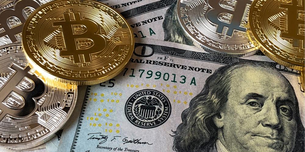 Dólares y monedas bitcoin en una mesa. Fuente: David McBee/ Pexels.com