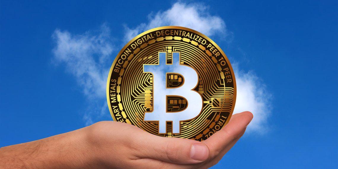 Bitcoin siendo alzado por una mano en un cielo despejado. Fuente: geralt/ Pixabay.com