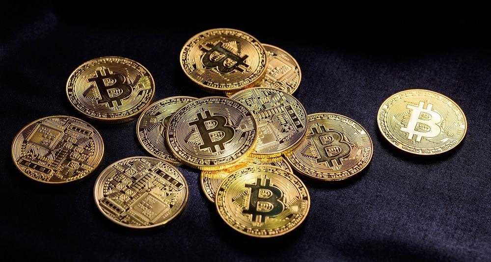 Grupo de monedas de bitcoin sobre tapete. Fuente: rawf8/elementes.envato.com