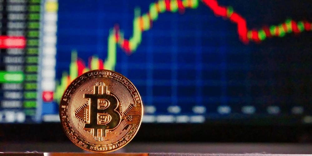 Un bitcoin delante de una gráfica de mercado de valores. Fuente: RoyBuri.