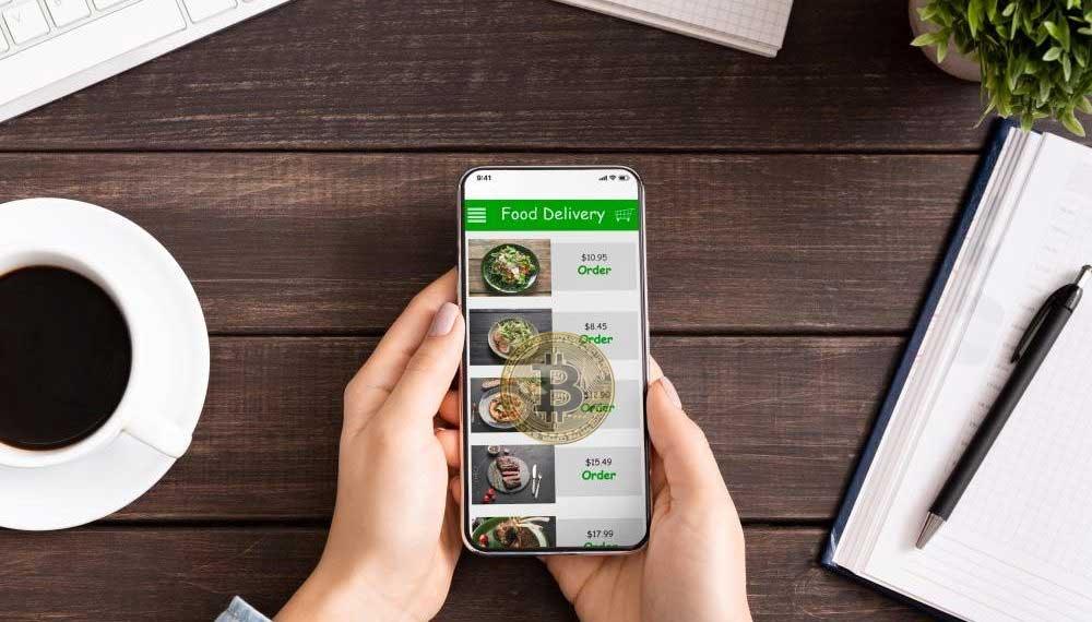 Usuario interactúa con aplicación de delivery que acepta pagos con bitcoin. Imágenes por Prostock studio y gargantopia/elements.envato.com