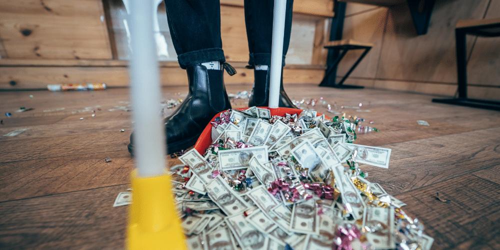 Una persona barriendo billetes de dólar falsos. Fuente: simbiothy/ Envatoelements.