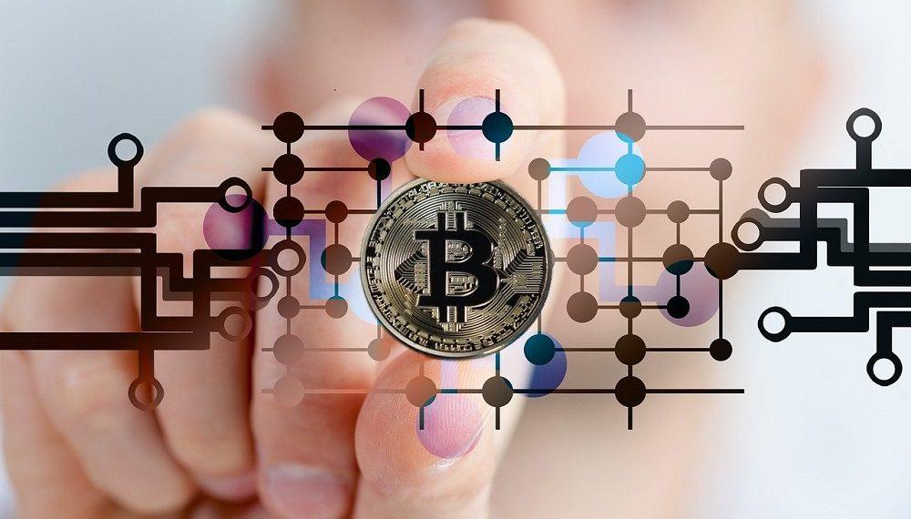 Mano de hombre con moneda bitcoin de plata. Fuente: Gerd Altmann/pixabay.com