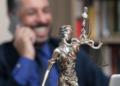 Abogado sonríe frente a una estatua miniatura de La Justicia. Fuente: leokiru/ Pixabay.com