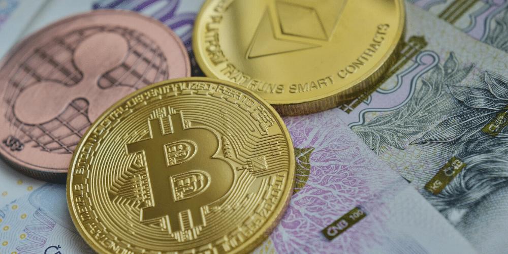 Bitcoin, Ripple y Ether en una mesa junto a dinero fiat. Funte: vjkombajn/ Pixabay.com