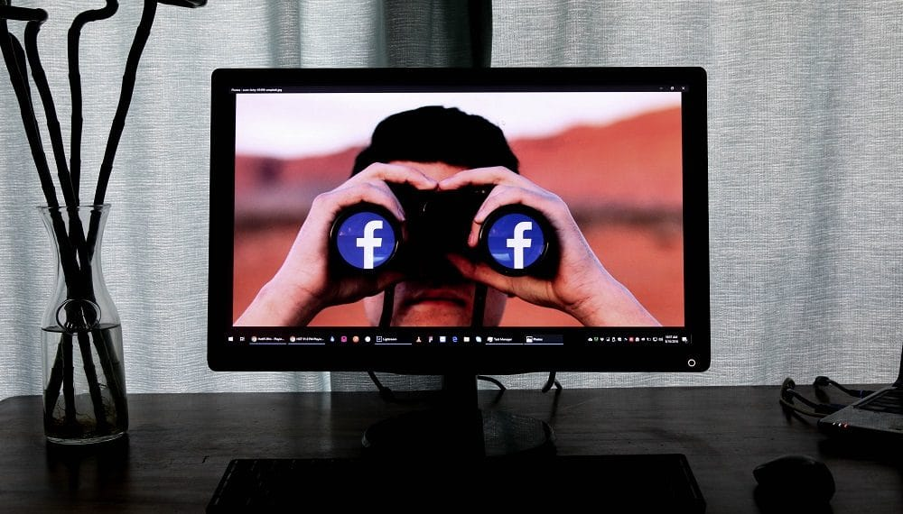 Hombre con binoculares y logo de Facebook. Fuente:  Glen Carrie/unsplash.com