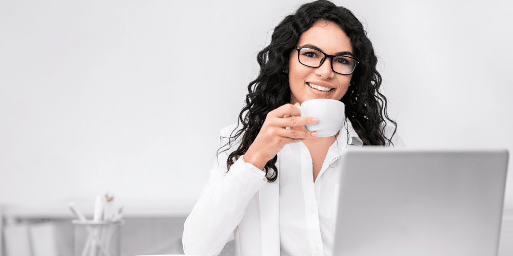 Una mujer toma café frente a un escritorio de trabajo. Fuente: Prostock-studio/ Envato Elements.