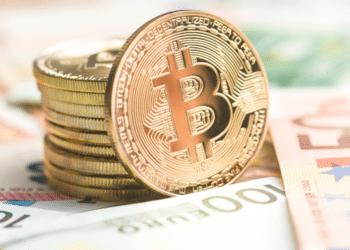 Un bitcoin entre billetes de euros. Fuente: jirkaejc/ Envato Elements.