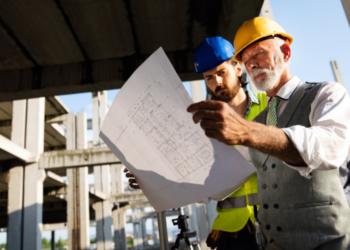 Un arquitecto revisa planos de un edificio en construcción. Fuente: nd3000/ Envato Elements.