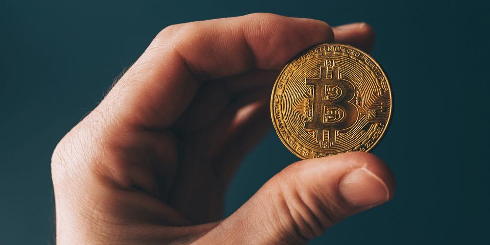 Una persona cargando un bitcoin. Fuente:  stevanovicigor/ Envato Elements.