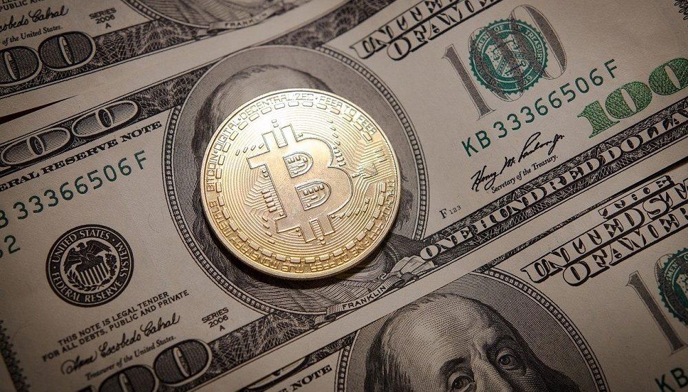 Moneda de bitcoin sobre billete de 100 dólares. Fuente: Petre Barlea/pixabay.com