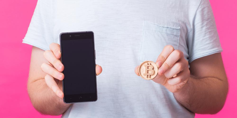 Un hombre enseña su bitcoin y teléfono celular. Fuente: Satura_/ Envato Elements.