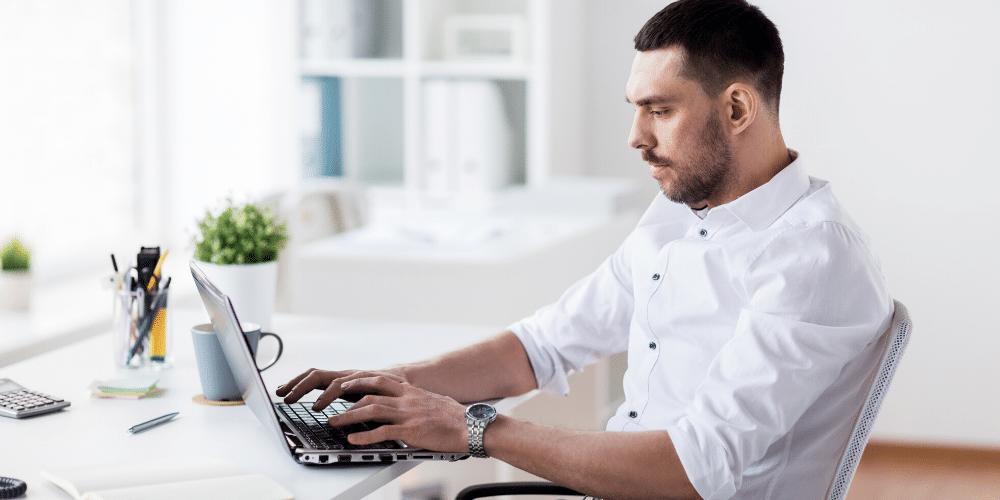 Una persona escribiendo en su computadora. Fuente: dolgachov/ Envato Elements.