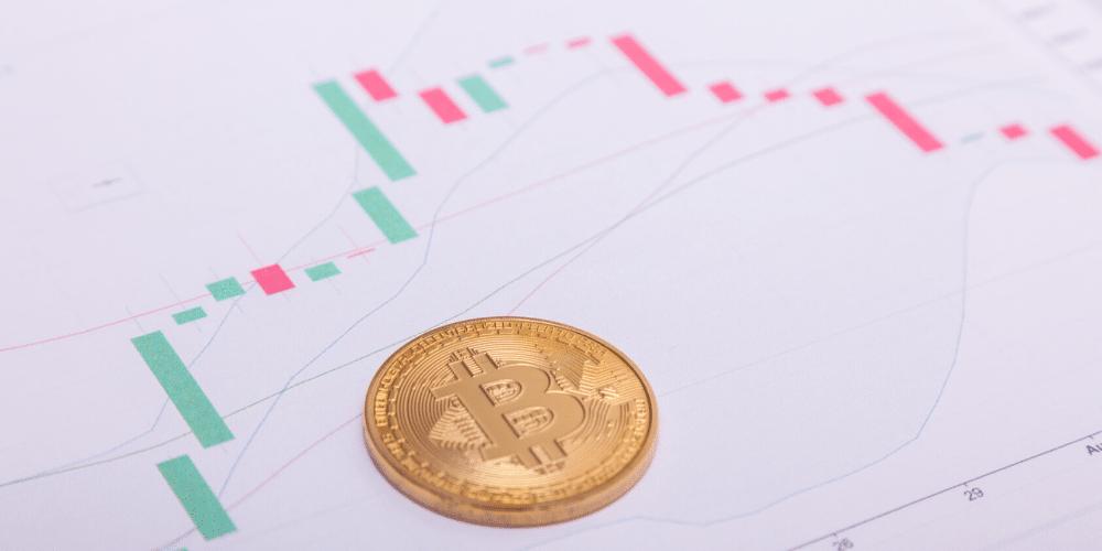 Un bitcoin sobre unas gráficas de trading. Fuente: sam741002/ Envato Elements.