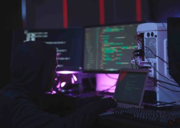 Portrait of unrecognizable hacker using computer equipment with programming code on screens in dark room, cyber security concept, copy space. Fuente: