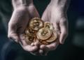 Una persona cargando un puño de monedas de bitcoins. Fuente: grafvision/ Envato Elements.
