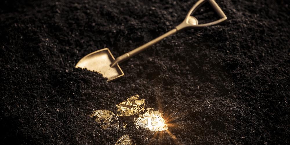 Una pala, tierra y monedas de bitcoin. Fuente: grafvision/ Envato Elements.