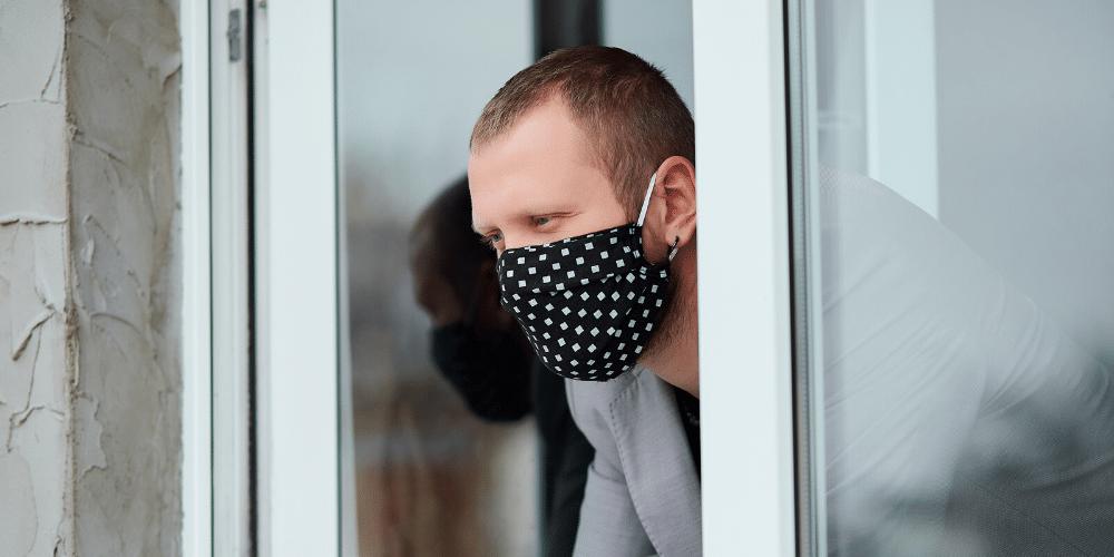 Un hombre mira por la ventana con mascarilla. Fuente: bondarillia/ Envato Elements.