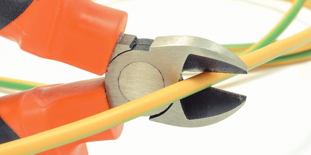 Un alicate cortando un cable de electricidad. Fuente: ratmaner/ Envato Elements.