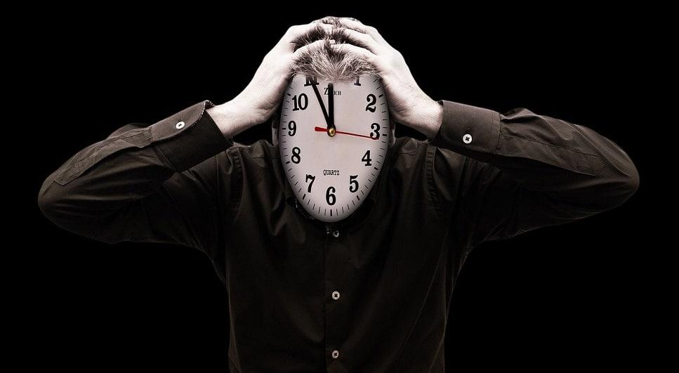 Hombre con cara de reloj sujetándose la cabeza con ambas manos. Fuente: Gerd Altmann / Pixabay