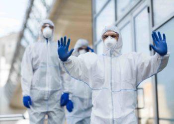 Hombre vistiendo traje protector contra el coronavirus haciendo gestos para detener a las personas. Fuente: Prostock-studio/ Envato Elements