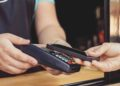 Persona realizando un pago por medio de su smartphone usando la tecnología NFC en una cafetería al aire libre. Fuente: KonstantinKolosov/ elements.envato.com