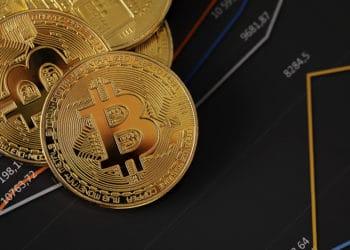 Criptomonedas bitcoin encima de estadísticas y gráficos financieros. Fuente: kjekol/elements.envato.com