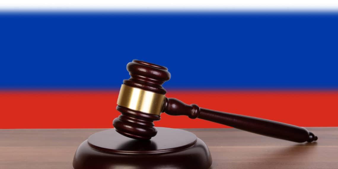 Martillo de juez sobre una base de madera, frente a la bandera de Rusia. Fuente: Marco Verch/Flickr.