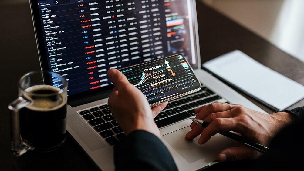 Hombre evaluando el mercado de las criptomonedas en la pantalla de un teléfono y en la computadora. Fuente: avanti_photo /   elements.envato.com