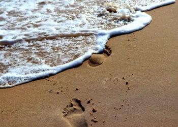 Huellas en la arena siendo borradas por el mar. Fuente: Thomas Gerlach /  Pixabay.com