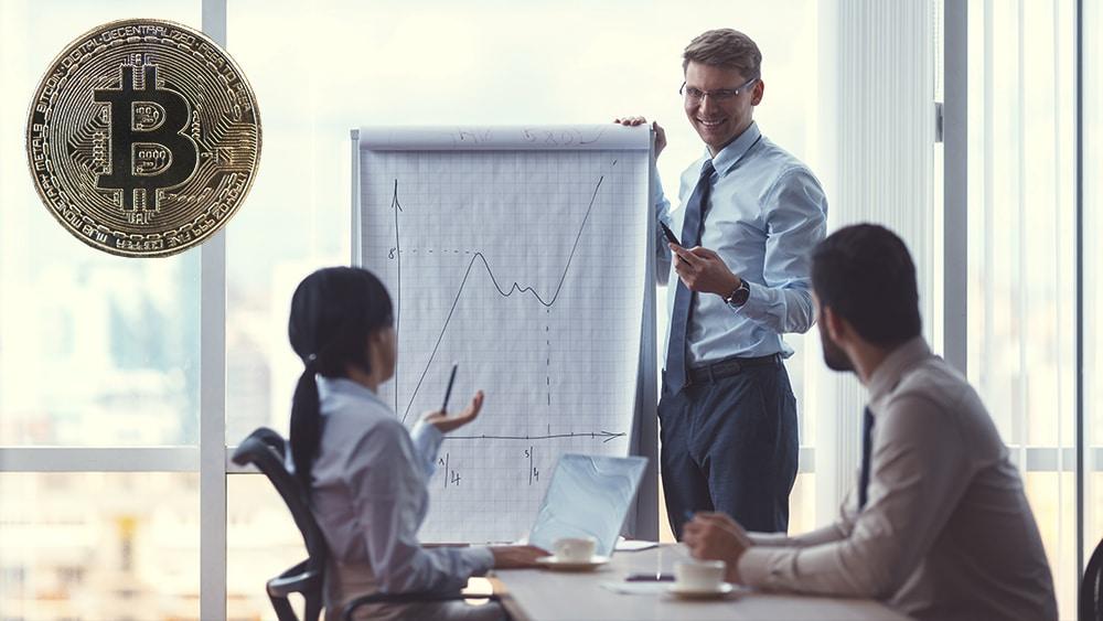 Empresario sonriente mostrando un rotafolio con curva ascendente a sus empleados, en la esquina bitcoin. Composición por CriptoNoticias  AboutImages / elements.envato.com ;   merc67 / elements.envato.com