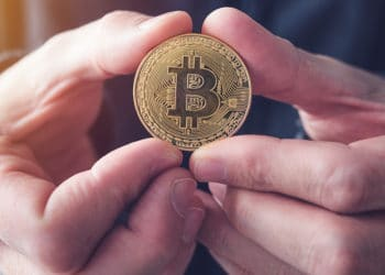 Hombre sosteniendo con ambas manos moneda de bitcoin. Fuente: stevanovicigor /   elements.envato.com