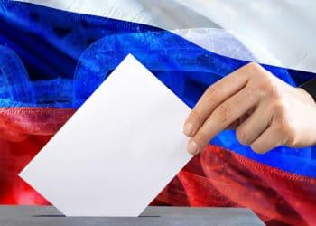 Mano votando con un fondo de bandera de Rusia sobrepuesto con cadena blockchain. Composición por CriptoNoticias erika8213 / elements.envato.com ; iLexx /  elements.envato.com ;  jorono /  pixabay.com