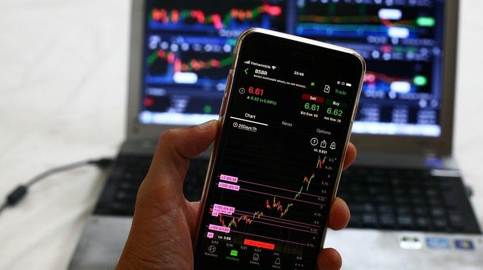 Mano sosteniendo un dispositivo con gráficas de mercado frente a una computadora. Fuente: Sergei Tokmakov, Esq. / Pixabay