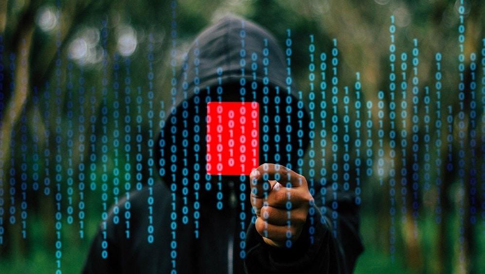 Persona con sweater negro enseñando una tarjeta roja entre filas de código binario. Fuente: Gerd Altmann / Pixabay