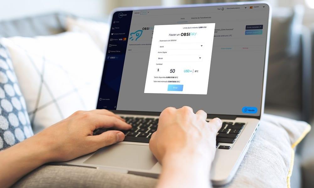 Persona que realiza un pago ObsiPay en una computadora portátil.