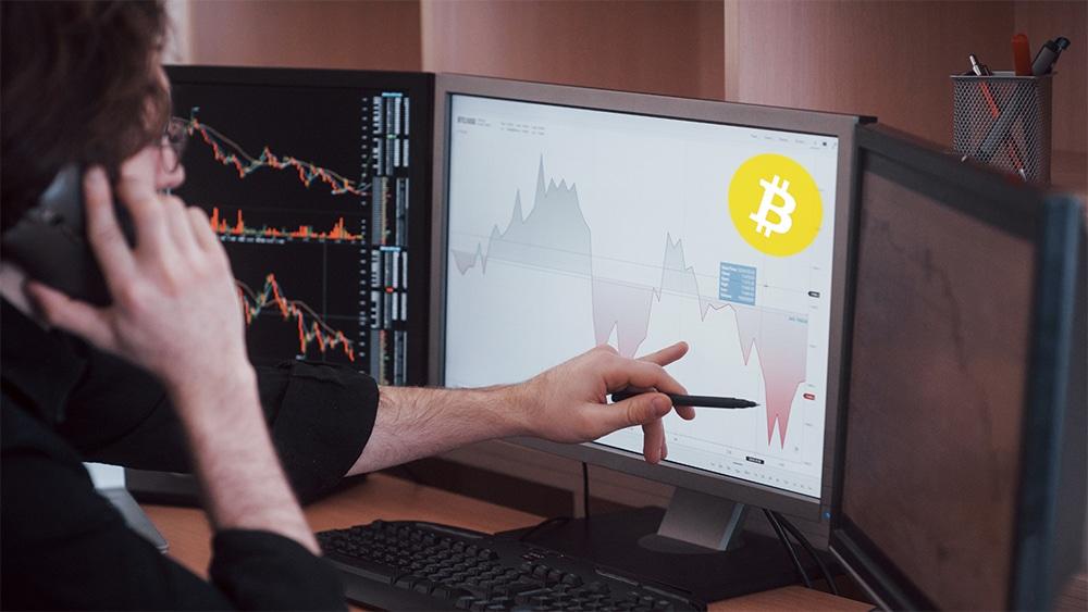 Trader señalando gráfico en pantalla con logo de Bitcoin. Composición por CriptoNoticias. WikimediaImages / Pixabay.com ; mstandret / elements.envato.com