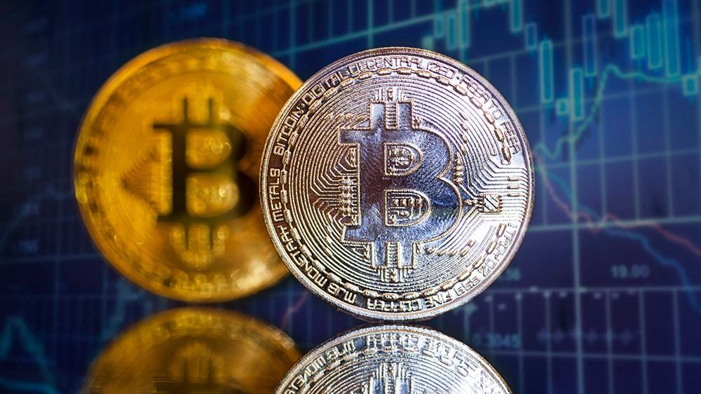 Monedas de Bitcoin frente a gráfico de velas en el fondo. Fuente: erika8213 / elements.envato.com