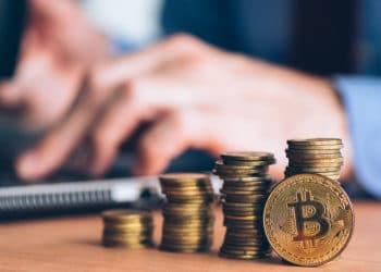 Moneda de Bitcoin con monedas apiladas y persona en su computadora en el fondo. Fuente: stevanovicigor / elements.envato.com