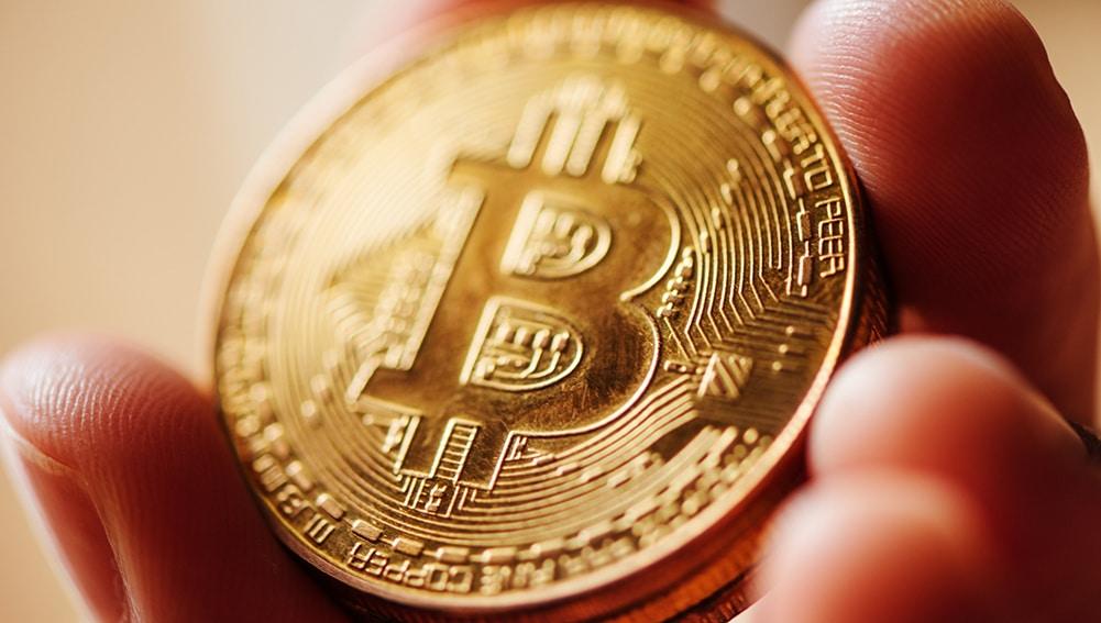 Hombre sosteniendo de cerca moneda dorada de Bitcoin. Fuente: stevanovicigor / elements.envato.com