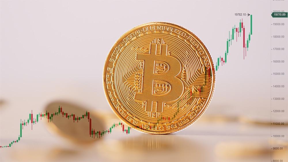Moneda de Bitcoin con grafico de mercado en el fondo. Composición por CriptoNoticias. leungchopan / elements.envato.com; Binance / Binance.com