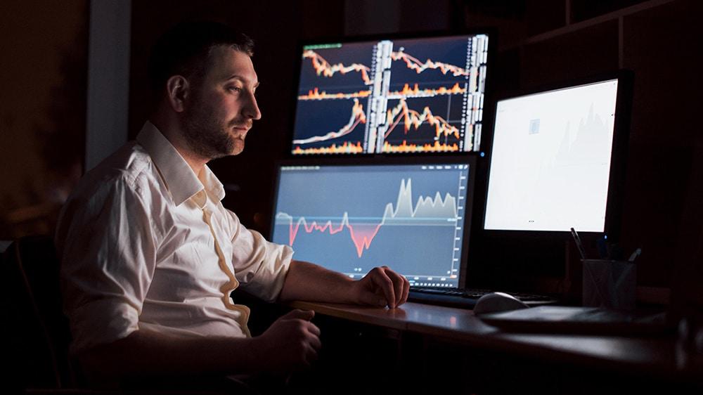 Trader en habitación oscura con gráficos de mercados en pantallas. Fuente: mstandret / elements.envato.com