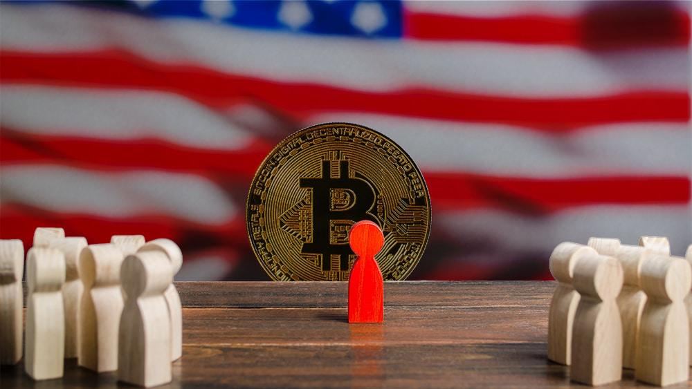 Figura de usuario discriminado con moneda de bitcoin frente a bandera de Estados Unidos de fondo. Composición por CriptoNoticias, jirkaejc / elements.envato.com; twenty20photos / elements.envato.com