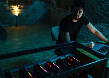 Hombre en la oscuridad con mineros de criptomonedas. Fuente: bernardbodo / elements.envato.com