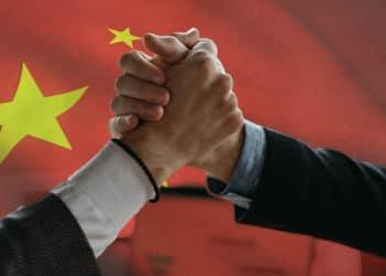 Hombres sosteniendo sus manos con bandera de China de fondo. Composición por CriptoNoticias. arthurhidden  / elements.envato.com; wirestock / Freepik.com